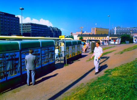 Harmaatakkinen mies seisoo bussipysäkin takana katse pysäkin seinää päin, selkä kameraan. Kuvan oikeassa alareunassa on nurmikkoa ja sorapolku, jota pitkin kävelee valkopaitainen ihminen pysäkkiä kohti. Aurinko paistaa ja taivas on sininen.