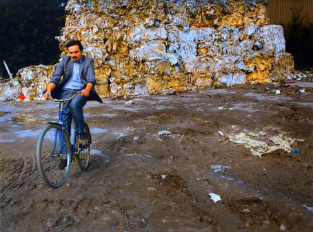 Harmaatakkinen, viiksekäs mies istuu sinisen pyörän selässä. Takana on roskia puristettuna isoiksi kuutioiksi ja kasattuna korkeiksi pinoiksi.