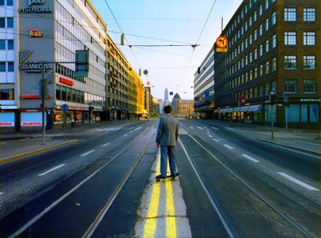 Harmaatakkinen mies seisoo skeittilaudan päällä keskellä tietä selkä kameraan päin. Tiessä on kahdet raitiovaunukiskot. Kadun molemmilla puolilla on kerrostaloja, kauempana olevia taloja valaisee aurinko.