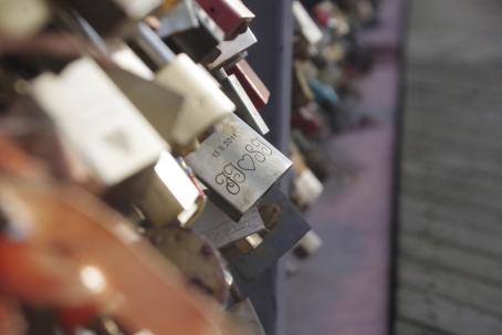 """Sillassa kiinni olevia lukkoja. Kuva on tarkentunut keskellä olevaan lukkoon, jossa lukee """"13.8.2011"""" ja koristeelliset nimikirjaimet."""