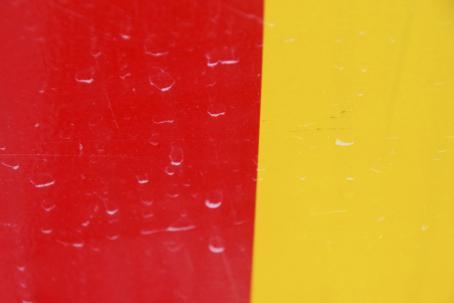 Vasen puoli on punainen ja oikea puoli keltainen, keskellä kulkee suora viiva hieman vinoon. Molemmilla puolilla on pieniä, haaleita valkoisia jälkiä.