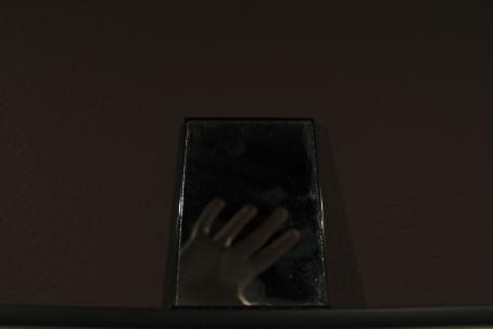Tumman kuvan keskellä on suorakulmion muotoinen peili, josta heijastuu epätarkkana ihmisen käsi sormet levällään.