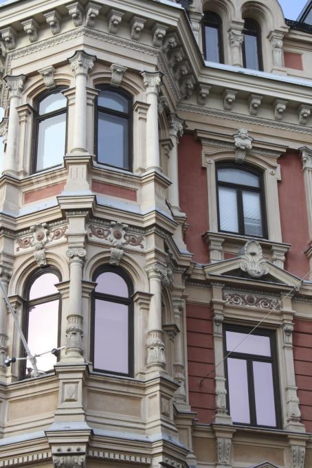 Kuva-alan peittää kokonaan yksityiskohta vanhasta, koristeellisesta vaaleanpunasävyisestä talosta. Kuvassa on talon seinässä oleva uloke ja ikkunoita.