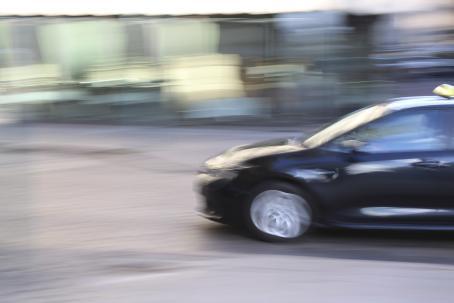 Oikealta kuvaan tulee musta taksi, joka näkyy kuvassa puoliksi. Kuva on liike-epäterävä.