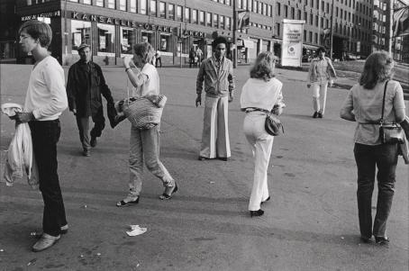 Mustavalkoisessa kuvassa kävelee ihmisiä aukiolla eri suuntiin. Keskelle on pysähtynyt nuori tummaihoinen mies leveälahkeisissa housuissa. Taustalla näkyy Kansallis-osake-pankin rakennus.