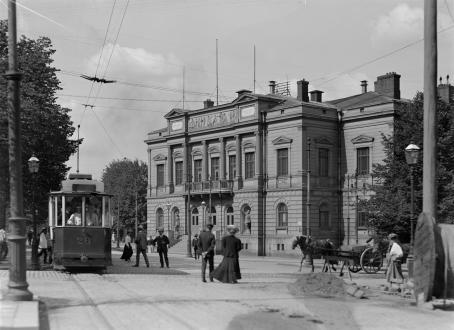 Mustavalkoinen vanha maisema Helsingistä. Vasemmalla on raitiovaunu, kadulla kävelee ihmisiä, siellä on myös hevoskärryt ja taustalla on koristeellinen rakennus, joka on Ylioppilastalo.