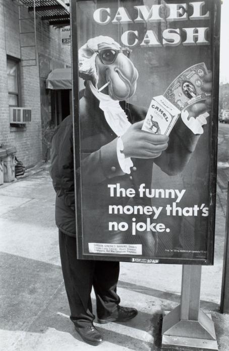 """Mustavalkoisessa kuvassa kadulla oleva mainos, jossa on ihmismäiseksi puettu kameli. Mainoksessa lukee """"Camel Cash, the funny money that's no joke"""". Mainoksen takana seisoo henkilö, joka on osittain piilossa mainoksen takana ja sulautuu mainoksessa olevaan kameliin."""