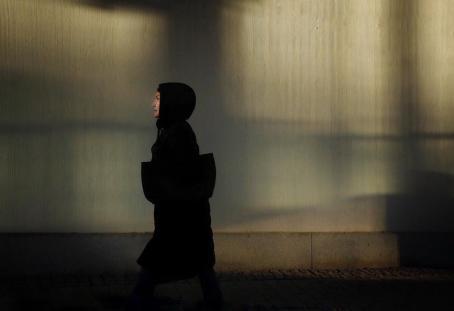 Mustaan takkiin pukeutunut henkilö olallaan musta laukku kävelee seinän edestä. Taustalla olevaan seinään heijastuu valoa kuin puiden tai jonkin muun läpi.