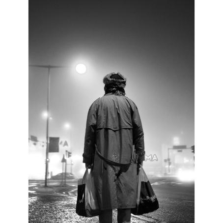 Mustavalkoisessa kuvassa on selin kameraan henkilö, jolla on päällään pitkä takki ja molemmissa käsissä muovikassit. Tausta on hämärä ja utuinen, katuvalot erottuvat valopalloina.