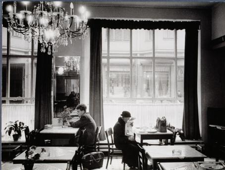 Mustavalkoinen näkymä kahvilasta tai ravintolasta. Kaksi ihmistä istuu eri pöydissä selätysten. Pöydissä ei ole muita ihmisiä. Heidän kohdallaan on iso ikkuna kadulle päin.