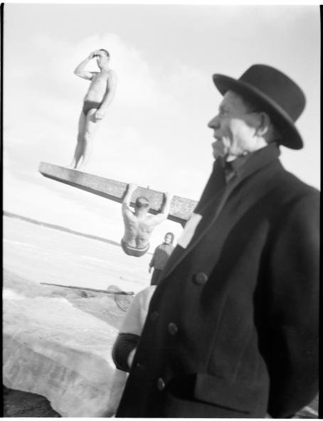 Mustavalkoisessa kuvassa etualalla seisoo mies sivuttain kameraan nähden, yllään tumma talvitakki ja hattu. Hänen takanaan on uimahyppylauta, jolla seisoo mies pelkät uimahousut jalassa. Toinen uimahousuinen mies roikkuu käsillä ja jaloilla laudan alapuolella. Maassa on lunta ja jäätä. Kuva on vino.