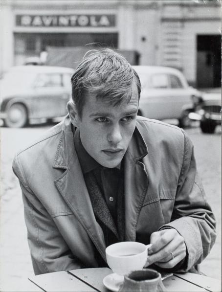Mustavalkoisessa kuvassa nuori, nahkatakkinen mies istuu ulkona ja pitelee kahvikuppia.