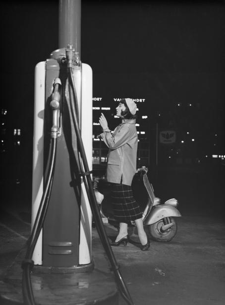 Mustavalkoisessa kuvassa nainen bensa-automaatilla. Hänen vieressään on skootteri. Ulkona on pimeää, naisen taustalla näkyvät korkean rakennuksen seinässä olevat valaistut yritysten nimet.