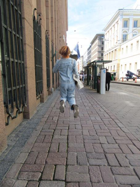 Henkilö hyppää ilmaan katunäkymässä.