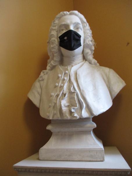 Kaisaniemen kasvitieteellisessä puutarhassa kuvattu patsas, jolla on koronamaski kasvoillaan.