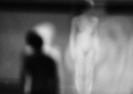 Mustavalkoisessa, epätarkassa kuvassa näkyy musta hahmo, ja sen takana kaksi valkoista hahmoa.
