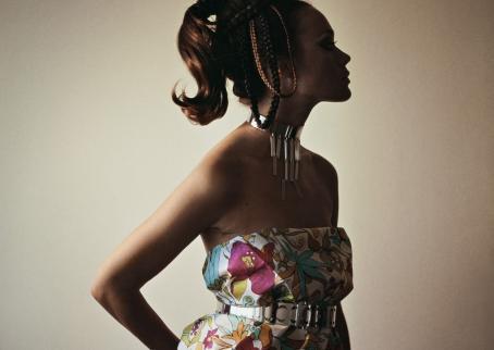Tummaihoinen nainen, jonka kasvot jäävät varjoon. Hänellä on päällään olkaimeton mekko ja kaulassa koruja.