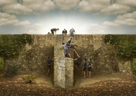 Korkea kivimuuri, jonka yli partiopojat ovat menossa. Osa on jo muurin päällä, osa auttaa toisia kiipeämään.