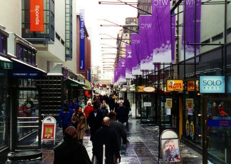 Näkymä kaupungin kadulta. Näkyy liikkeiden mainoksia ja paljon ihmisiä.