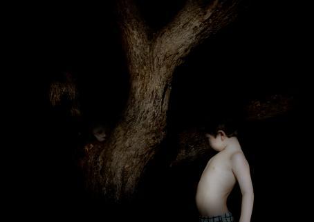 Muuten täysin musta, mutta keskellä on puu ja sen vieressä hyvin valaistu poika ilman paitaa. Puun takaa näkyy myös toiset kasvot.