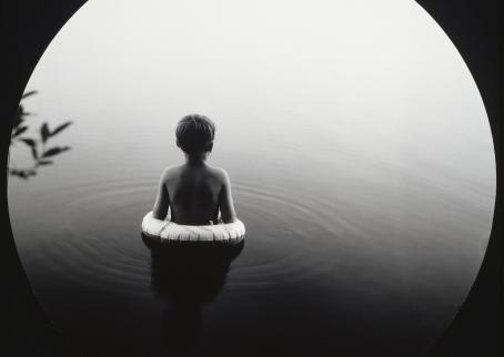 Mustavalkoisessa kuvassa lapsi uimarenkaan kanssa tyynessä vedessä.