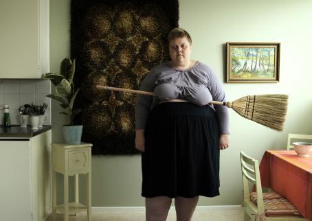 Isokokoinen nainen (Iiu Susiraja) violetissa paidassa ja mustassa hameessa seisoo keittiössä. Hänellä on luuta poikittain rintojen alla. Nainen katsoo lähes suoraan kameraan, ehkä hieman ohi. Kuvan vasemmassa reunassa näkyy osa tiskipöytää, oikeassa reunassa osa ruokapöytää.