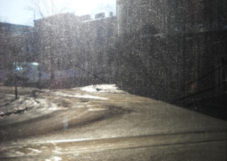 Likainen ikkuna, jonka läpi näkyy sumeasti tietä sekä rakennuksia.