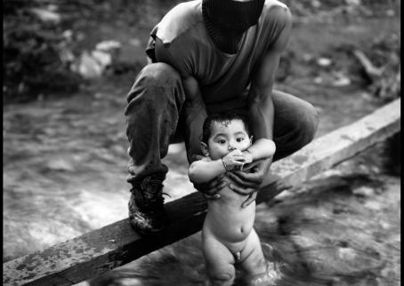 Mustavalkoisessa kuvassa kommandopipoinen henkilö uittaa alastonta poikavauvaa virtaavassa purossa.