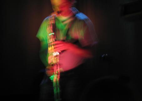 Hieman tärähtäneessä kuvassa henkilö soittaa saksofonia. Kuvassa näkyy vihreän ja vaaleanpunaisen sävyjä.