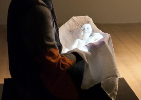 Henkilö istuu pitäen sylissään liinaa, johon heijastuu vauvan kuva.