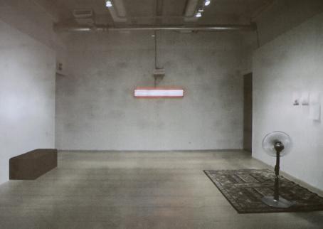 Lähes tyhjä huone. Vasemmalla seinustalla on ruskea suorakulmion muotoinen penkki, takaseinällä on pitkänomainen lamppu ja oikealla seinustalla on maton päällä tuuletin ja seinällä papereita.