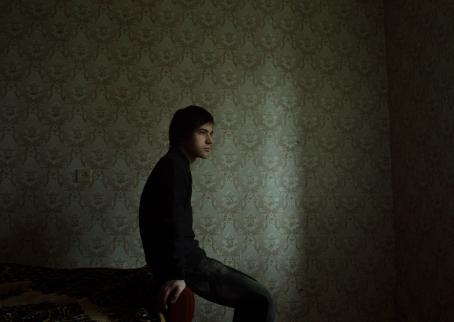 Tummassa kuvassa henkilö istuu nojaten sohvaan. Luultavasti ikkunasta tulee valoa häneen ja takana olevaan seinään.