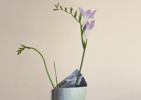 Vaaleaa taustaa vasten kukka purkissa, jota näkyy vain vähän, ja joka näyttää olevan tehty paperista.