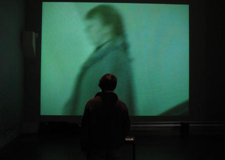Näyttelyssä kävijä istuu pianon ääressä ja katsoo teosta.