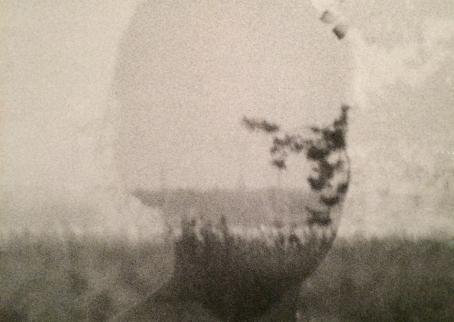 Mustavalkoisessa kuvassa naisen silhuetti, jonka läpi näkyy metsäistä maisemaa.