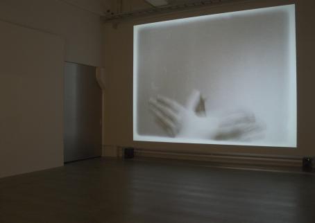 Näyttelytilassa seinälle heijastettu teos, jossa näkyvät yhteen liitetyt kädet.
