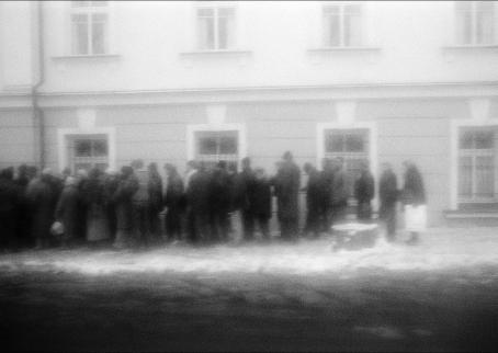 Rakeisessa, mustavalkoisessa kuvassa jono ihmisiä rakennuksen edessä.
