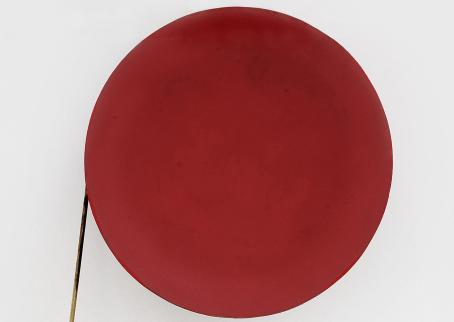Vaaleaa taustaa vasten iso punainen ympyrä, jonka vasemmalta puolelta lähtee alaspäin suora keppi tai tikku.