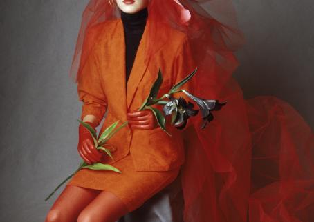Malli istuu tummanoranssit tai punaiset vaatteet päällään ja punainen huntu joka laskeutuu hänen vierelleen.