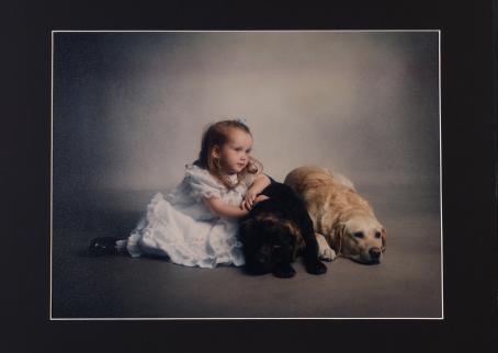 Pieni tyttö vaaleansinisessä mekossa poseeraa lattialla kahden koiran kanssa.