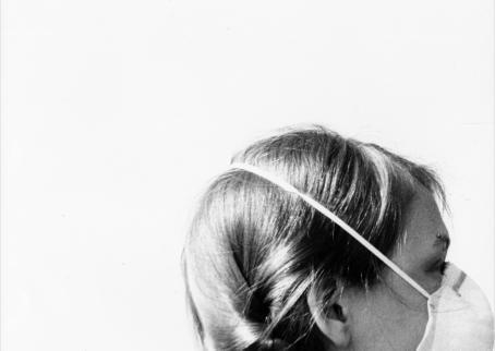 Vaaleaa taustaa vasten ihminen, jolla on hengityssuojain päässä. Hänestä näkyy vain pää.