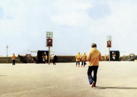 Keltatakkisia, sinihousuisia ihmisiä avoimessa maisemassa. Vasemmassa ja oikeassa reunassa menee silta.