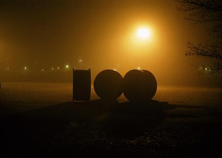 Tummassa maisemassa keskellä kolme isoa pyöreää objektia, joita valaisee takaapäin katulampun kellertävä valo.