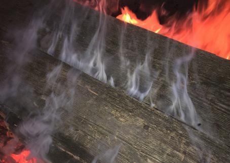 Kaksi leveää lautaa, joiden välistä tulee savua. Lautojen reunoilla näkyy liekkejä.