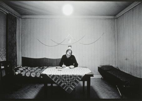 Mustavalkoinen kuva huoneesta. Huoneen keskellä on pöytä, jonka ääressä henkilö istuu kirjoittamassa paperille.