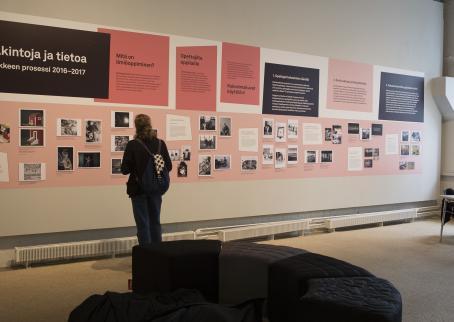 Museokävijä katsomassa näyttelyä. Seinällä on paljon kuvia ja tekstilaatikoita.