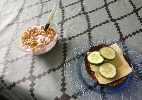 Ruudullisen pöytäliinan peittämällä pöydällä on kulhossa vaaleanpunaista jogurttia jonka seassa on muroja. Vieressä on lautasella ruisleipä, jonka päällä on juustoa ja kurkkua.