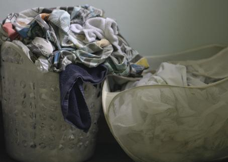Kaksi pyykkikoria. Ensimmäinen pursuilee yli, toinen on myös melko täynnä.