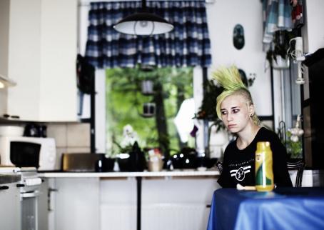 Nuori henkilö, jolla on vihreä irokeesi, istuu keittiönpöydän ääressä.
