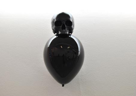 Musta ilmapallo, jonka päällä on palloa pienempi musta pääkallo.